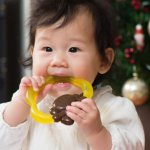 Teething Facts & Tips- Cute baby girl chewing on a teething ring
