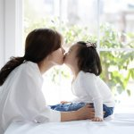 Does Kissing Cause Cavities In Children?- Young mom kissing her daughter on the mouth